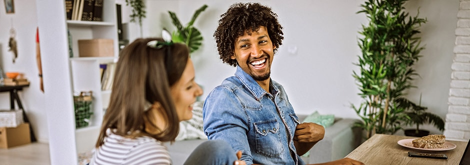 Couple smiles and laughs while sitting at their desk, considering all of the factors affecting the value of their home and helping to build equity