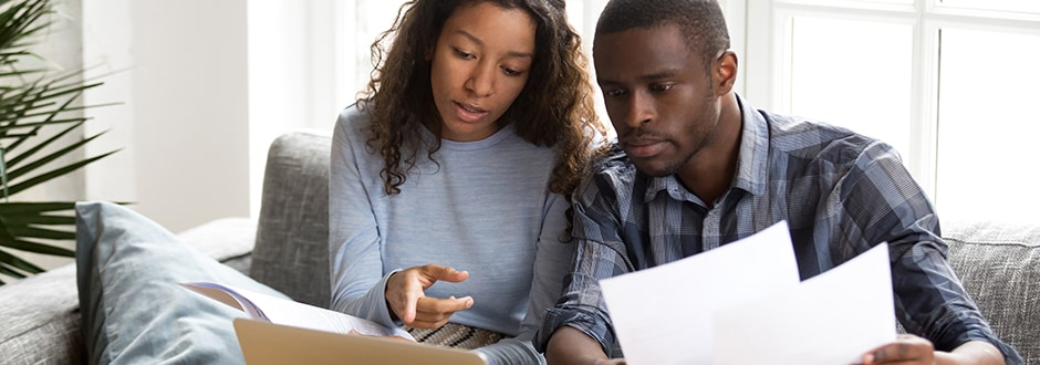 Young couple with computer and home purchase contract in hand discussing if it is a good time to walk away.