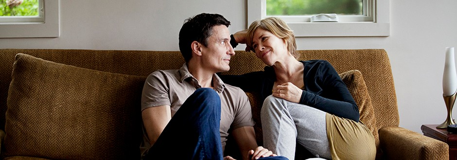 Couple sitting in home discussing home equity loans vs. HELOCs as consider the pros and cons of each