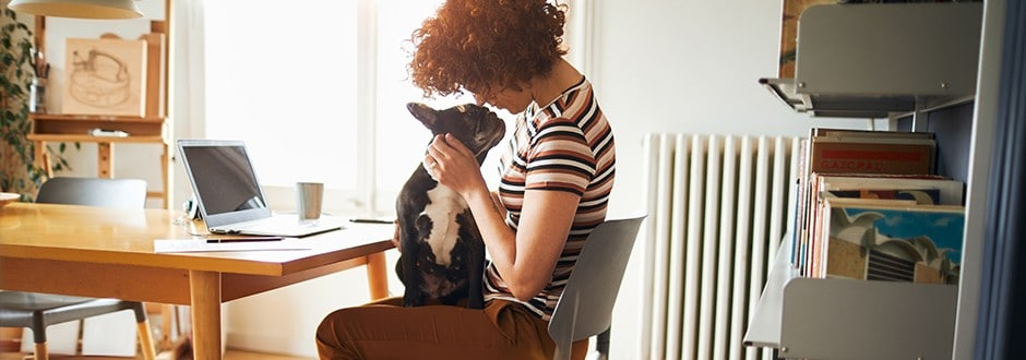 Woman plays with her dog while taking a break from evaluating her options to pay off debt