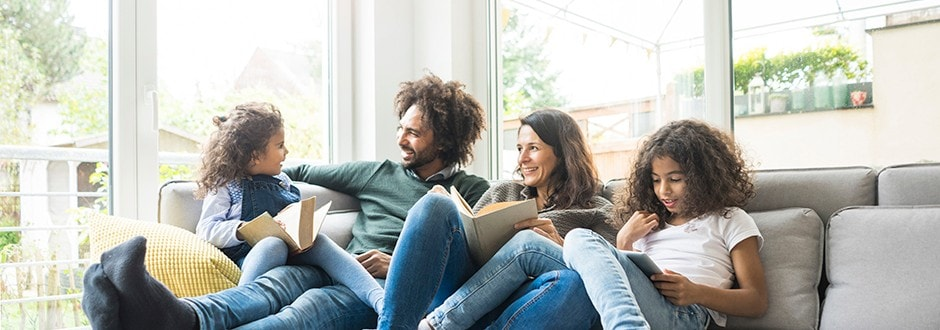 Family sitting on couch relaxed and happy that they lowered their mortgage payment.