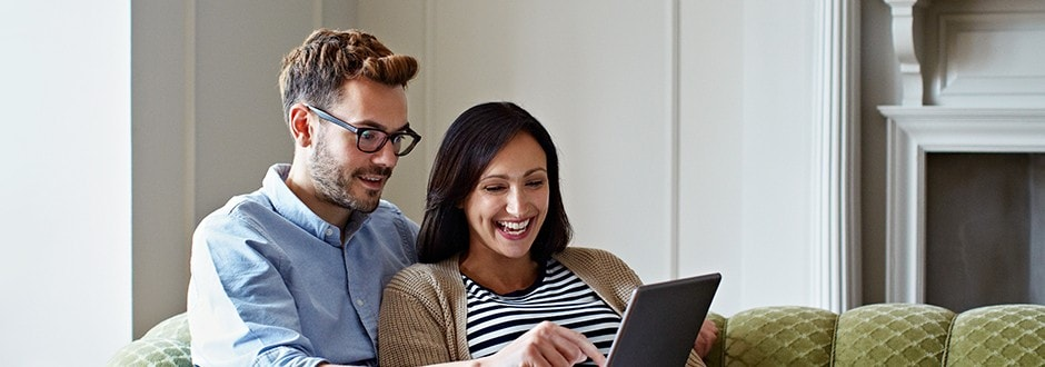 Couple on their computer researching the best season to buy a home