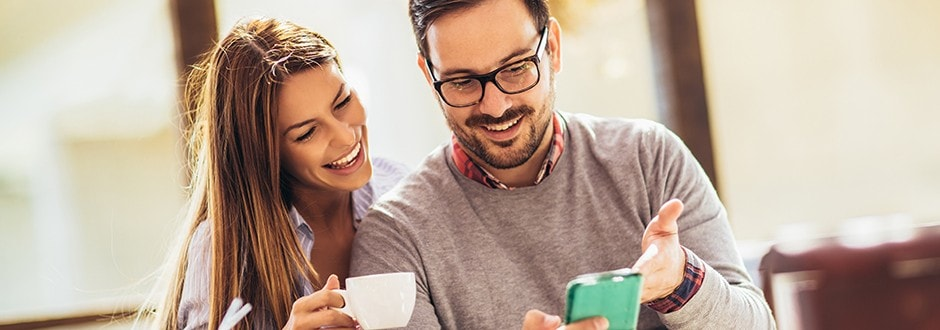 man and woman drinking coffee in their house discussing saving money and taking steps towards financing their future