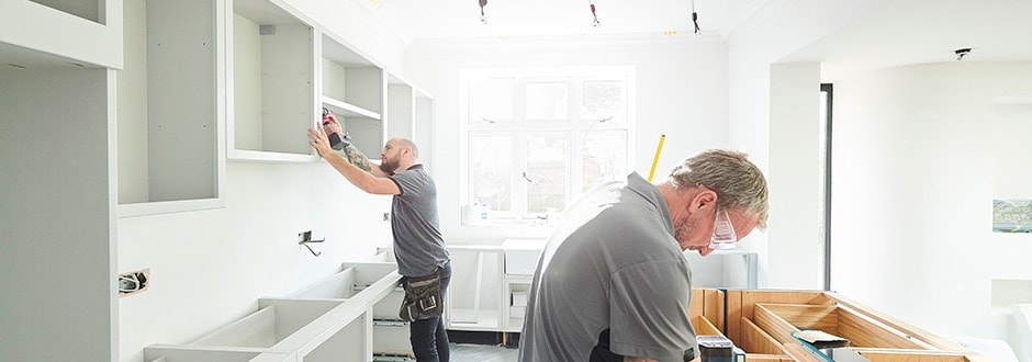 Construction workers installing cabinets in a kitchen that has been well thought out and funded using helpful tools