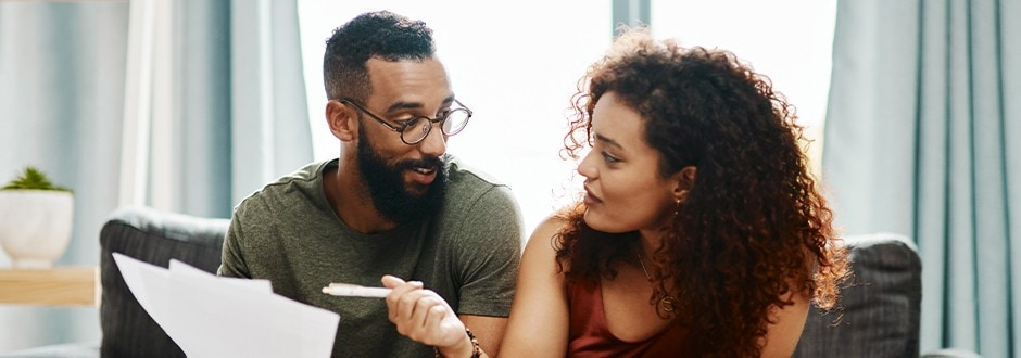 Couple looking at their documents calculating their debt to income ratio