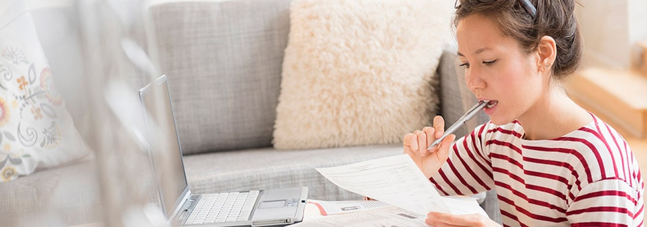 Woman sits on the floor of her living room reading getting and understanding of her home appraisal report