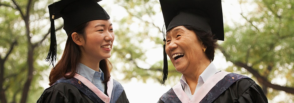 Two graduate school students smile and laugh at their graduation ceremony