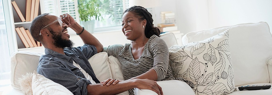 Family in living room laughing while they discuss what a second mortgage is as well as the benefits risks and other options