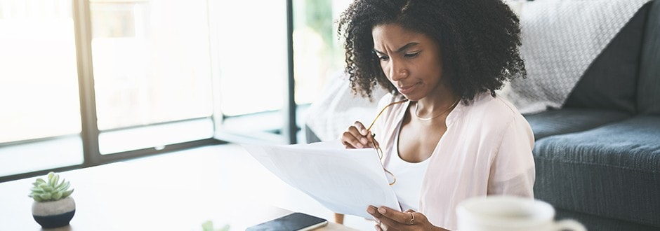 Woman evaluating paperwork researching how to terminate a purchase mortgage agreement