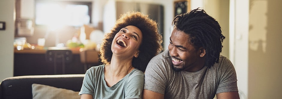 Couple laughing and joking while they discuss if it is time to stop renting and purchase a home