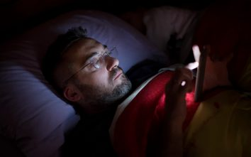 Man laying in bed on his smartphone - Modern Life