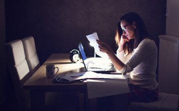 Woman sitting at her desk at night paying bills - Modern Life