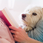 a woman reading a book with a dog laying on her