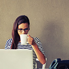 a woman drinking from a mug as she looks at her laptop