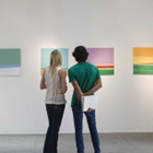 two people in a gallery looking at art
