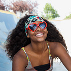 woman wearing heart-shaped sunglasses and smiling