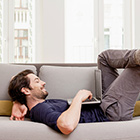 man relaxing on couch looking at laptop