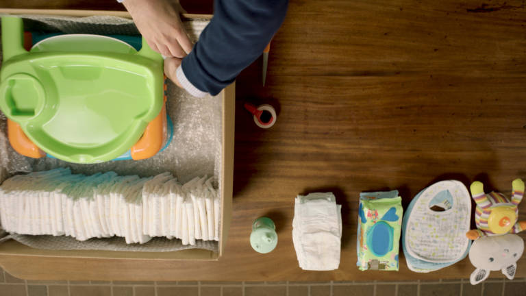 Father packs diapers and high chair for shipping