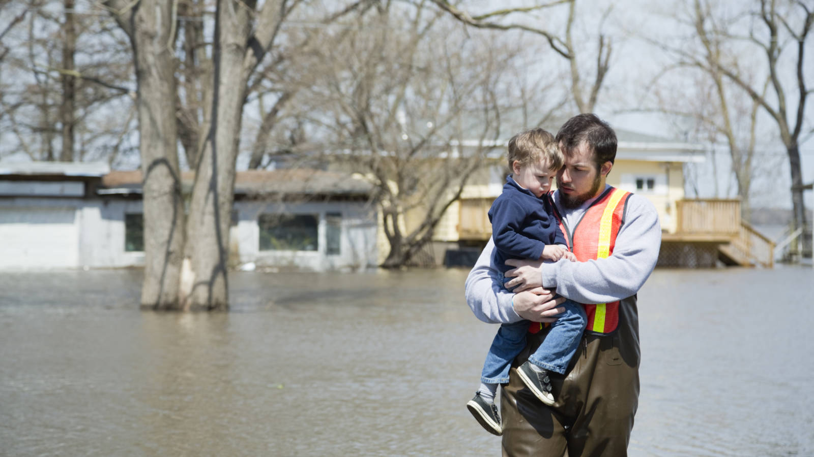 father wading through flood with his son
