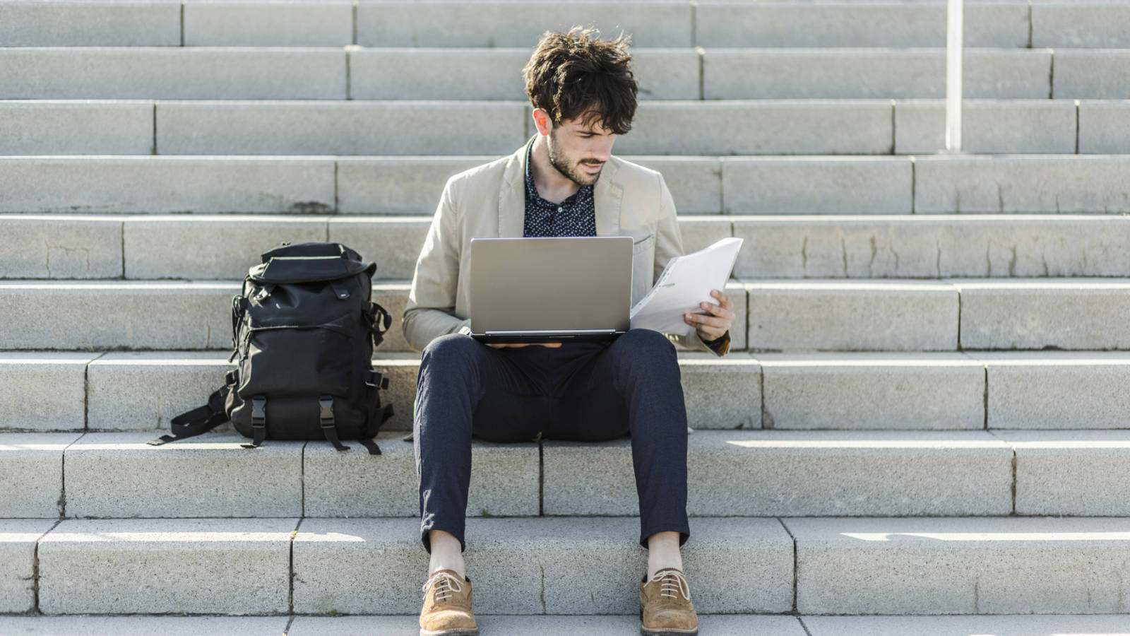 Young man on steps looking at laptop and papers