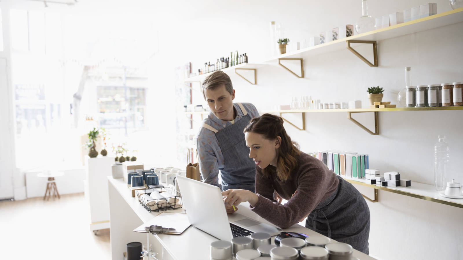 Shop owners using laptop in home fragrances shop