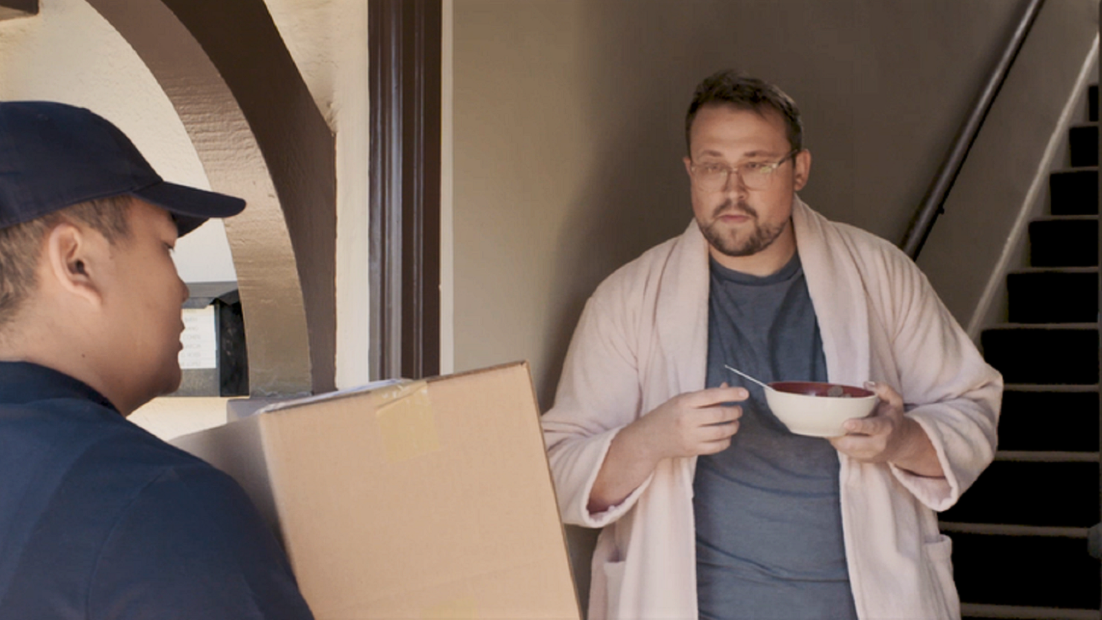 man in bathrobe receiving package delivery