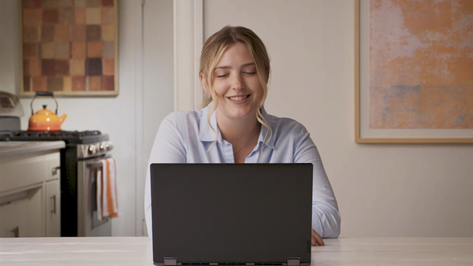 woman smiling while looking at her laptop
