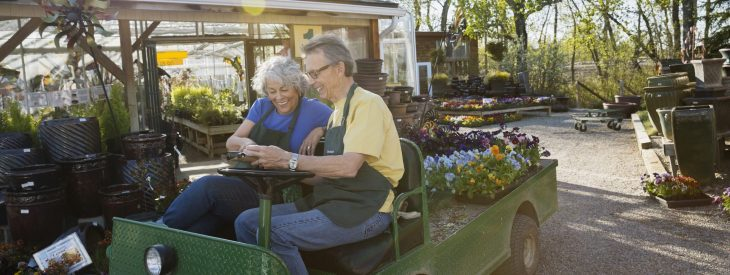 Older couple working in a garden nursery