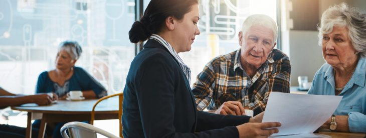 Retired couple meeting with a financial advisor to discuss withdrawal strategies