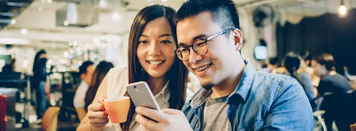 Couple looking at compounding interest calculations on a mobile phone