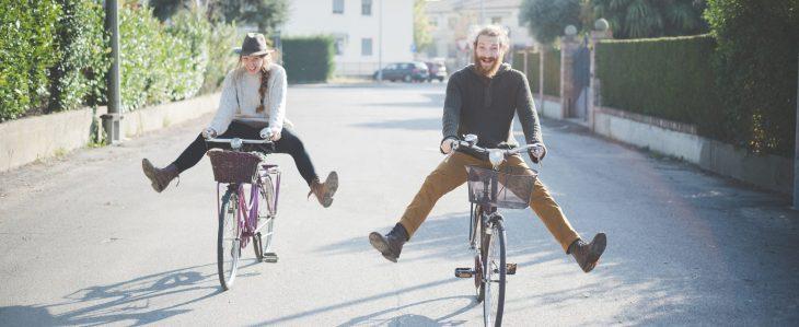 Man and woman having fun while riding bikes