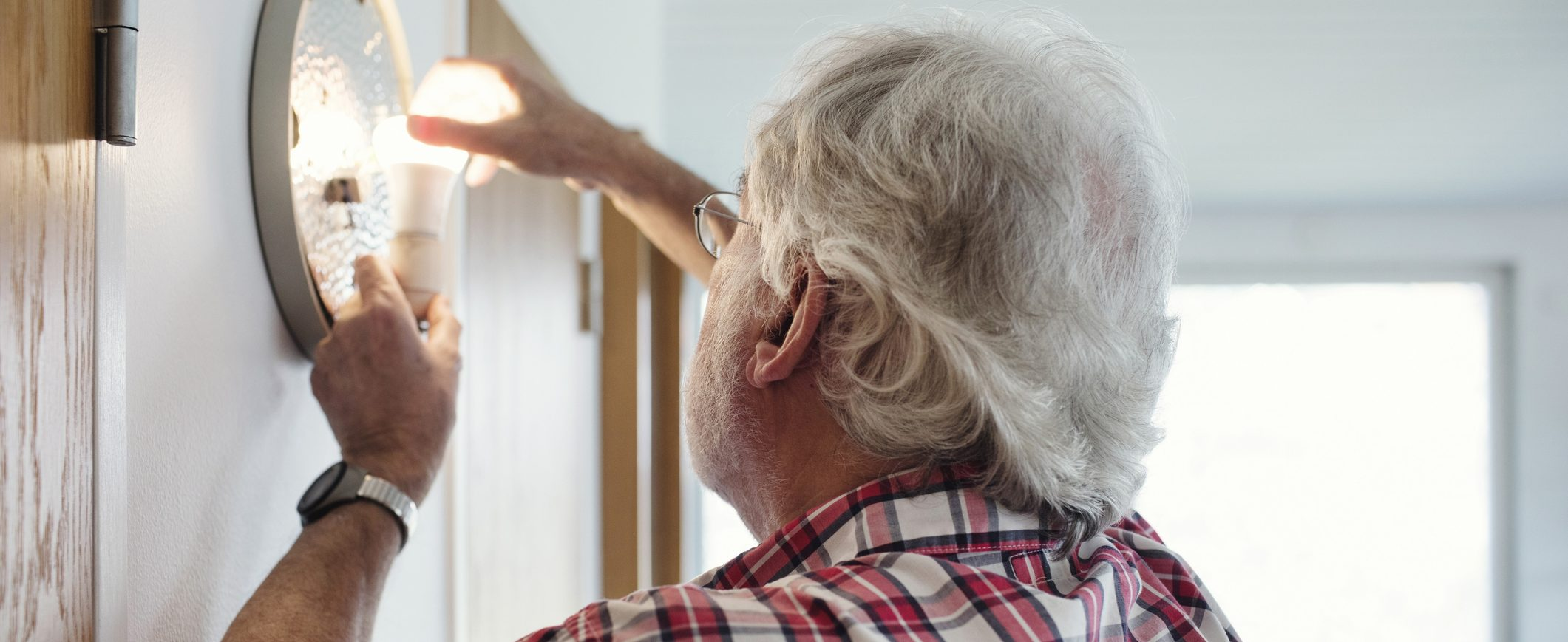 Man installs energy efficient light bulbs to help save money