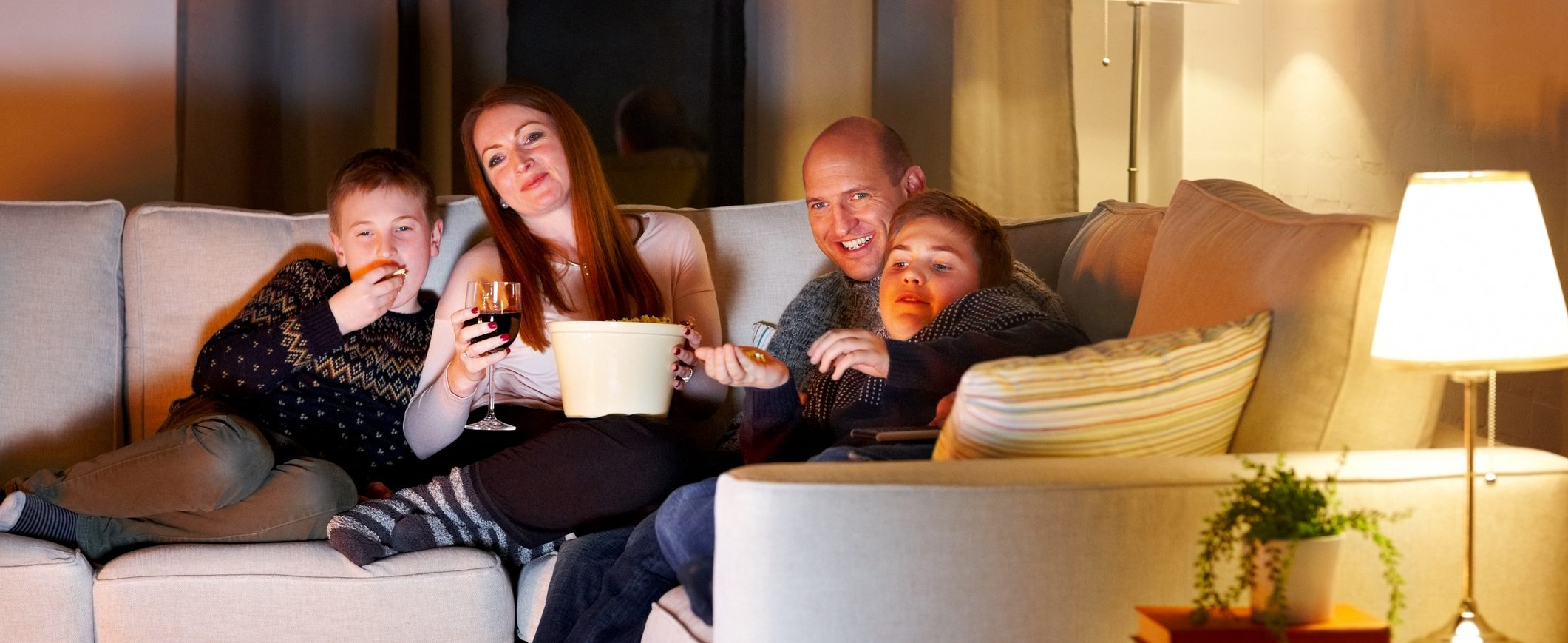 A family enjoys an evening at home rather than spending extravagantly on entertainment