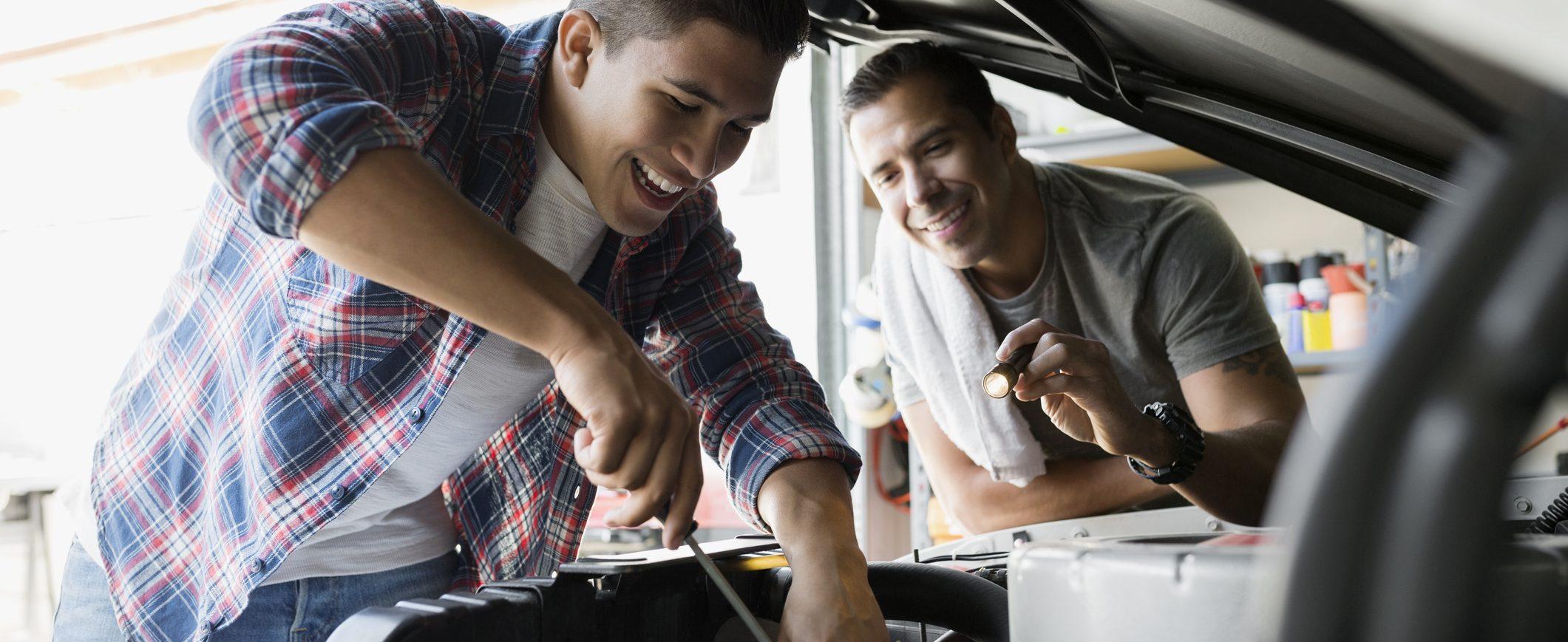 Father teaching his son how to repair a car