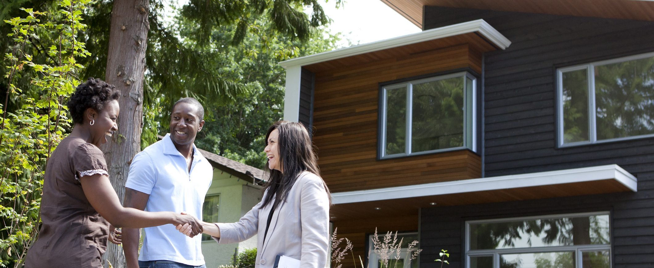 A young couple shakes hands with their real estate agent as they reach their financial goal of buying a house